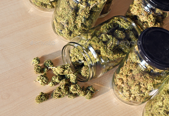 Dry and trimmed cannabis buds stored in a glas jars. - Stock Photo - Images