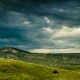 A Whirlwind of Dark Clouds Over Green Hills - VideoHive Item for Sale