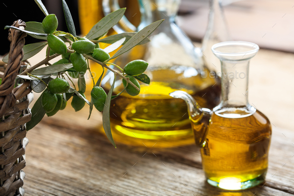 Olive oil and olive twig on a table - Stock Photo - Images