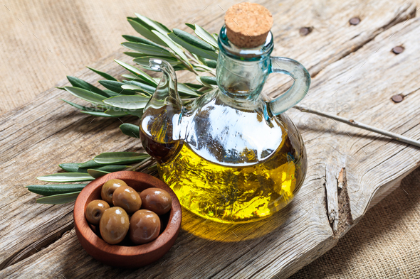 Bottle of olive oil and olives on a table - Stock Photo - Images