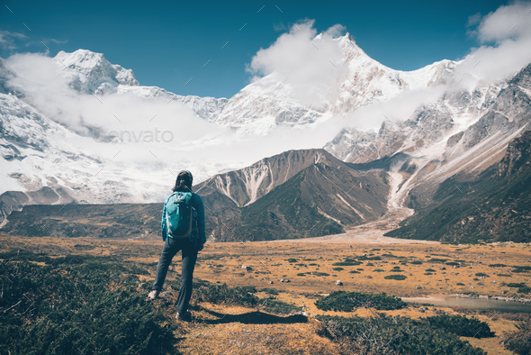 Woman with backpack looking on snow covered mountains - Stock Photo - Images