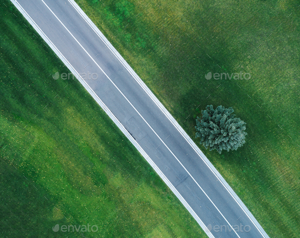 Aerial view of road through beautiful green field - Stock Photo - Images