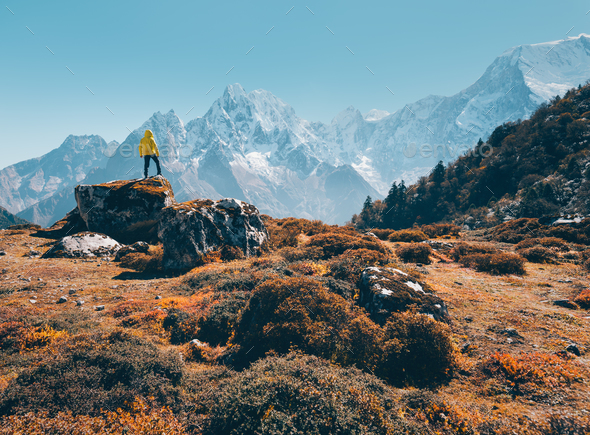 Standing man on the stone against snowy mountains - Stock Photo - Images