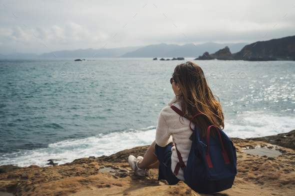 Female Traveler sitting and looking on sea waves - Stock Photo - Images