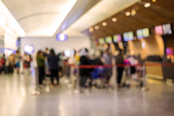 Blurred image of passengers wait in a queue for check-in in the airport - Stock Photo - Images