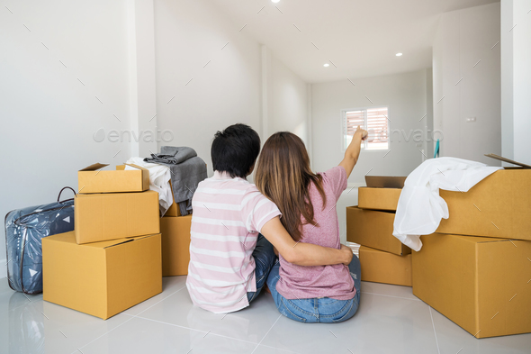 Young asian couple moving into new home together - Stock Photo - Images