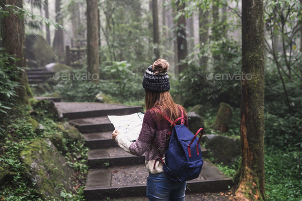 Young woman traveler looking map and walking in the nature education area - Stock Photo - Images