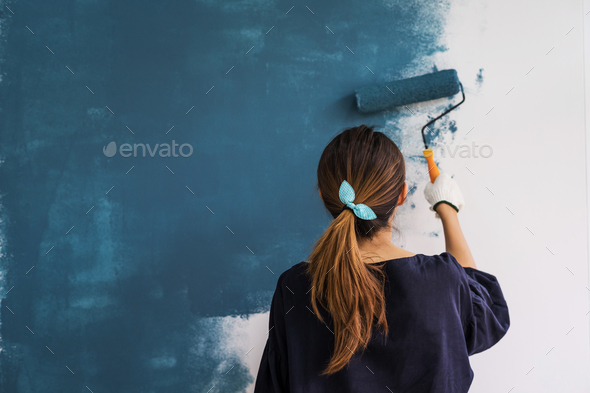 Young asian happy woman painting interior wal - Stock Photo - Images