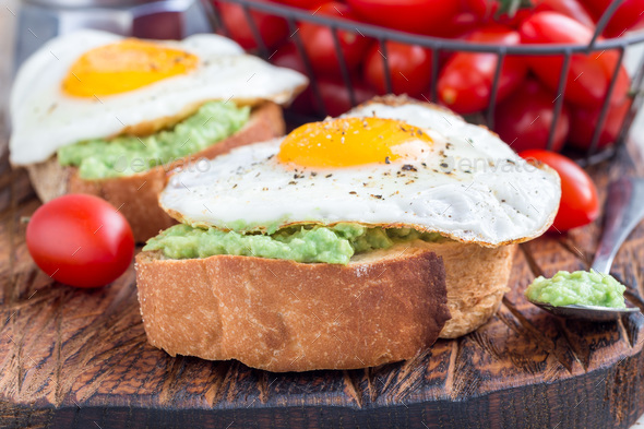 Open sandwiches with mashed avocado and fried egg on bread, horizontal - Stock Photo - Images