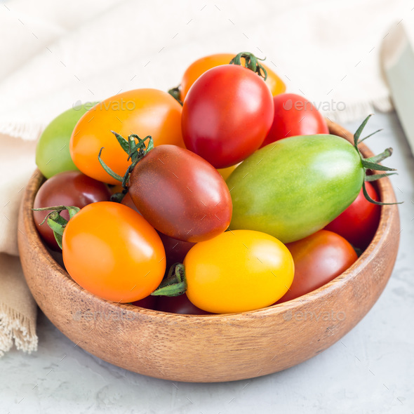 Small colorful cherry tomatoes in wooden bowl on table, square format - Stock Photo - Images
