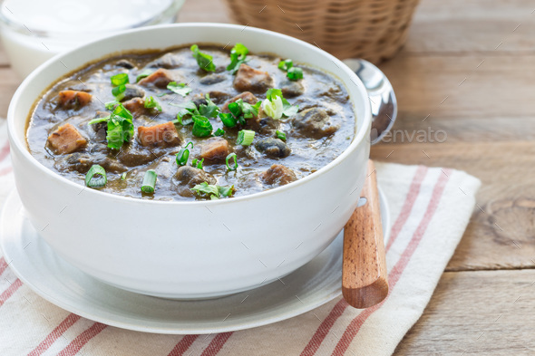 Homemade black bean and ham soup in ceramic bowl on wooden table, horizontal, copy space - Stock Photo - Images