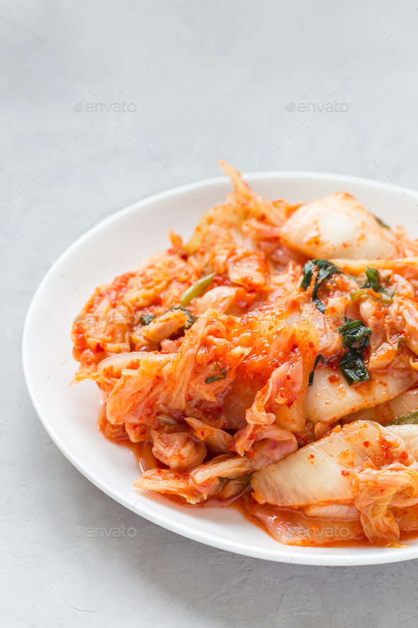 Kimchi cabbage. Korean appetizer on white plate, vertical, copy space - Stock Photo - Images
