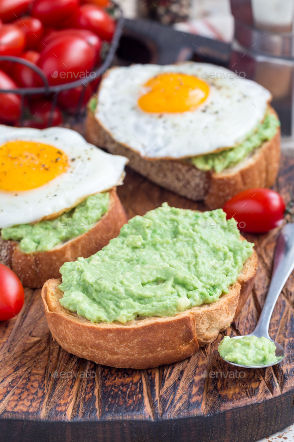Making open sandwiches with mashed avocado and fried egg on bread, vertical - Stock Photo - Images