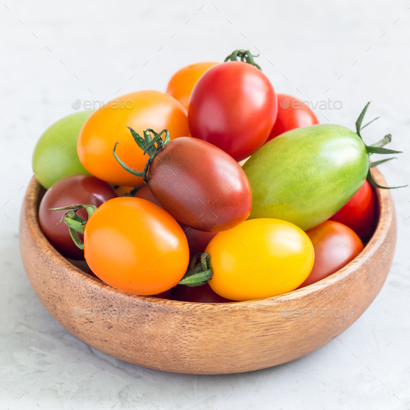 Small colorful cherry tomatoes in wooden bowl on a table, square format - Stock Photo - Images