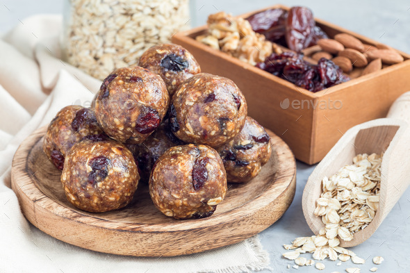 Homemade energy balls on wooden plate, horizontal - Stock Photo - Images