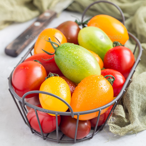 Small colorful cherry tomatoes in metal basket, square format - Stock Photo - Images