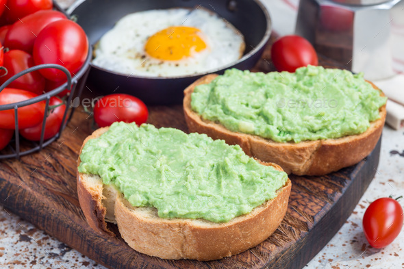 Open sandwiches with mashed avocado on toasted bread, fried egg in pan on background, horizontal - Stock Photo - Images