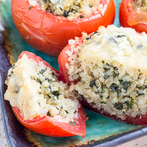 Baked tomatoes stuffed with quinoa and spinach topped with melted cheese, square format - Stock Photo - Images