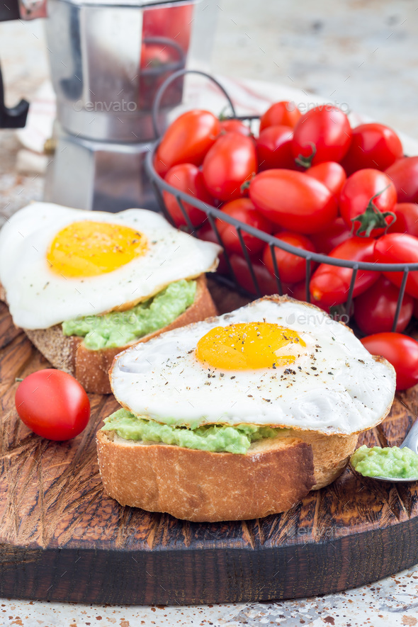 Open sandwiches with mashed avocado and fried egg on bread, vertical - Stock Photo - Images
