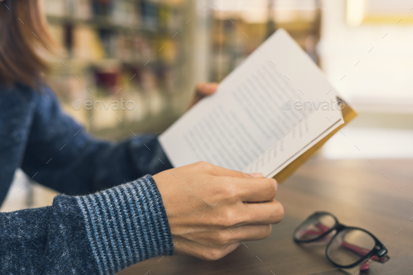 Close up of female hands open book in library - Stock Photo - Images