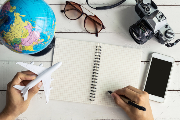 Traveler planning trip on notebook and smart phone - Stock Photo - Images