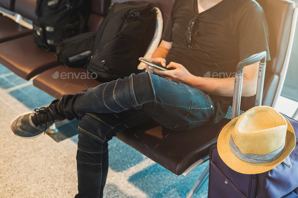 Young traveler using smartphone while waiting at the airport - Stock Photo - Images