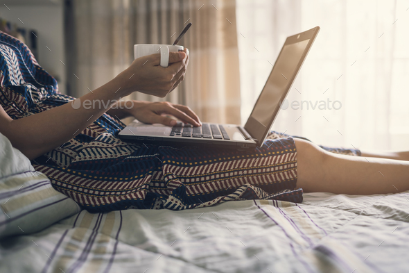 Young woman drink of coffee and using laptop computer - Stock Photo - Images