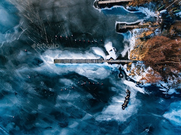 Aerial view of the winter frozen lake with wooden piers captured with a drone in Finland. - Stock Photo - Images