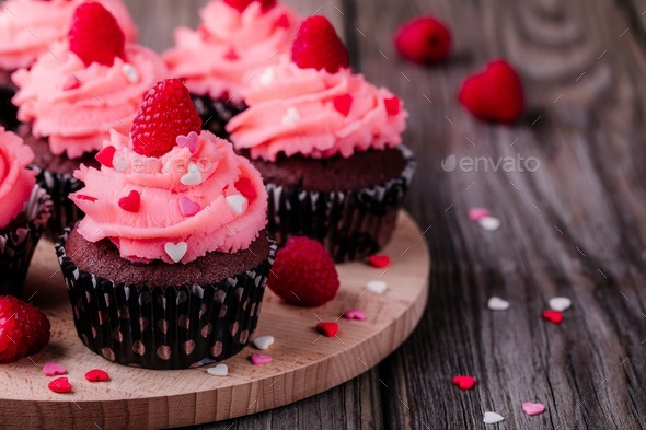 Chocolate cupcakes with pink cream, sugar hearts and fresh raspberries for  Valentine Day - Stock Photo - Images