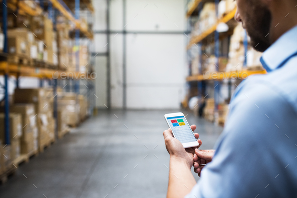 Man warehouse worker with a smartphone. - Stock Photo - Images