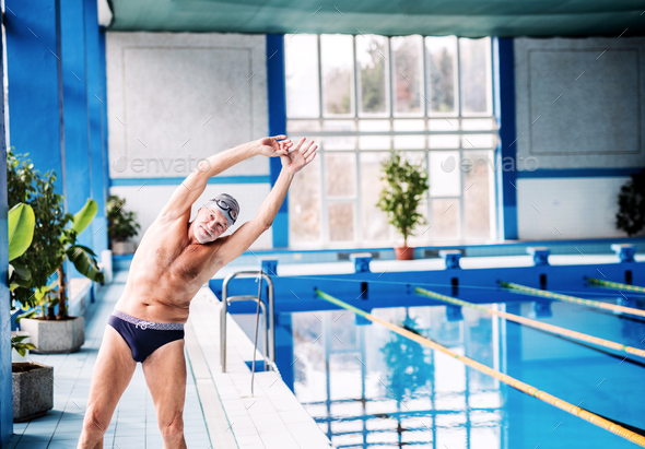 Senior man stretching by the indoor swimming pool. - Stock Photo - Images