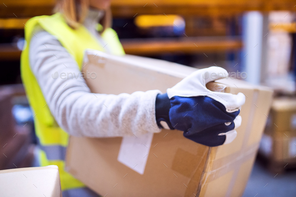 Female warehouse worker loading boxes. - Stock Photo - Images
