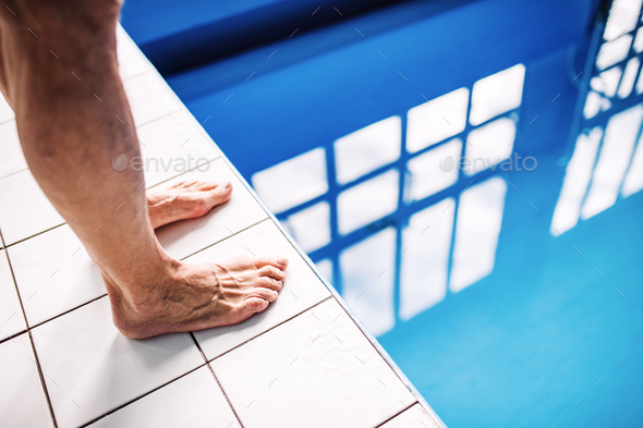 Legs of a man standing on the edge of the swimming pool. - Stock Photo - Images