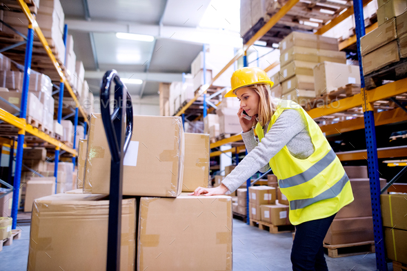 Woman warehouse worker with a smartphone. - Stock Photo - Images