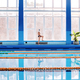 Senior man stretching by the indoor swimming pool. - PhotoDune Item for Sale