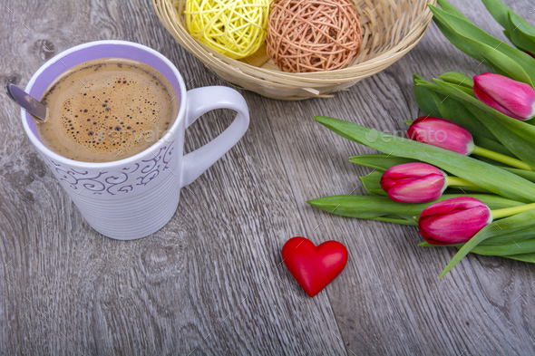 A cup of coffee and tulips on a wooden table - Stock Photo - Images