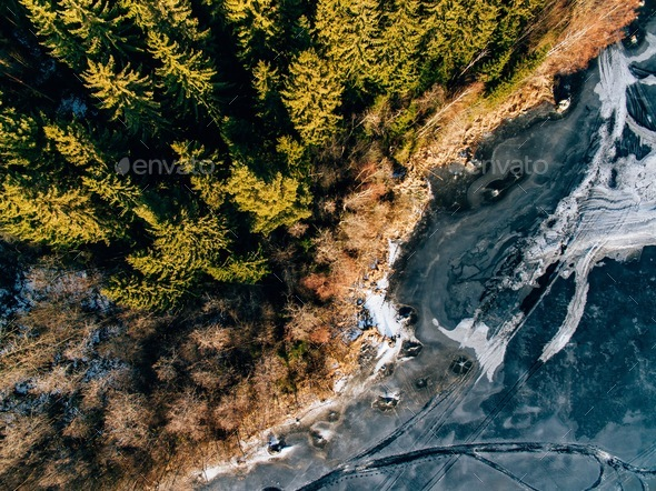 Aerial view of the winter snow forest and frozen lake from above captured with a drone in Finland. - Stock Photo - Images