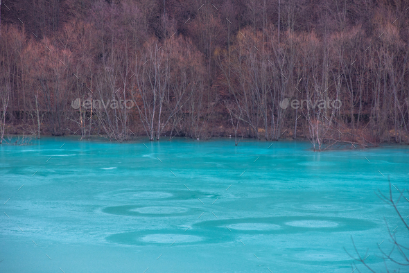 Turquoise waste lake contaminated mining residuals. The lake drowned the village of Geamana - Stock Photo - Images