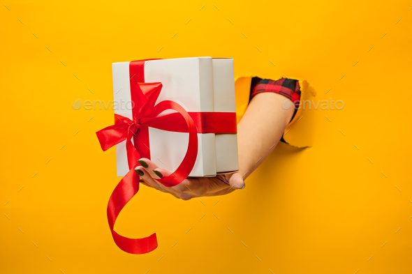 close-up of female hand holding a present through a torn paper, isolated - Stock Photo - Images