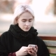 Blonde Girl Looks at the Smartphone Sits on a Bench Gets Text in Smartphone Calm Facial Expression - VideoHive Item for Sale