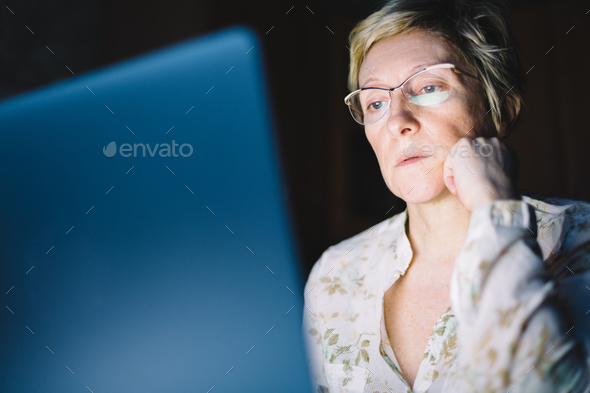 Middle-aged woman working on laptop - Stock Photo - Images