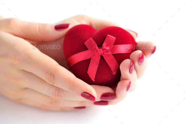 Beautiful female hands with red manicure holding a box of heart- - Stock Photo - Images