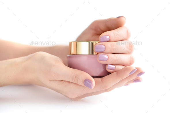 Hands of a woman with pink manicure with jar of cream on white b - Stock Photo - Images