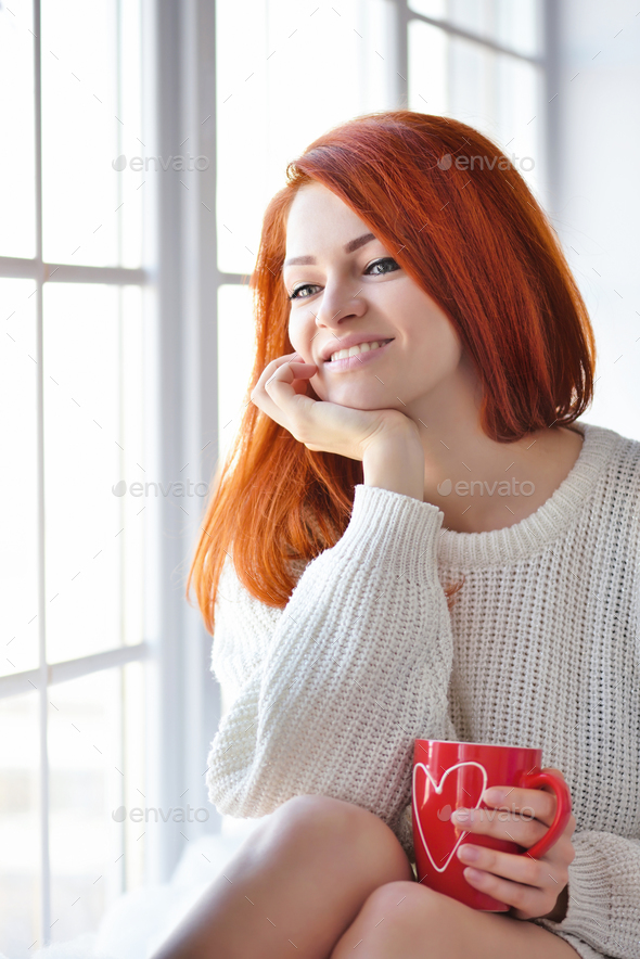 Beautiful red-haired woman near window with red mug in hands - Stock Photo - Images