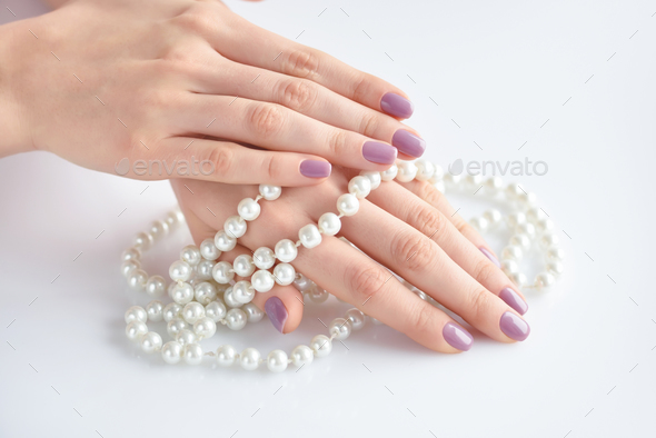 Beautiful hand of a young woman with pink manicure holding white - Stock Photo - Images