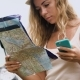 Blonde Girl in a Hat, Sits on a Bike and Looks at the Phone and a Map, Looks at the Route in Asia - VideoHive Item for Sale