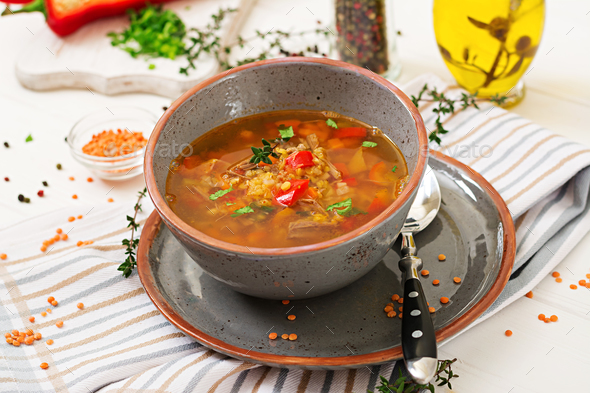 Appetizing soup with red lentils, meat, red paprika and fragrant thyme - Stock Photo - Images