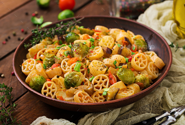 Vegetarian Vegetable pasta Rocchetti with brussels sprouts, tomato, eggplant and paprika - Stock Photo - Images