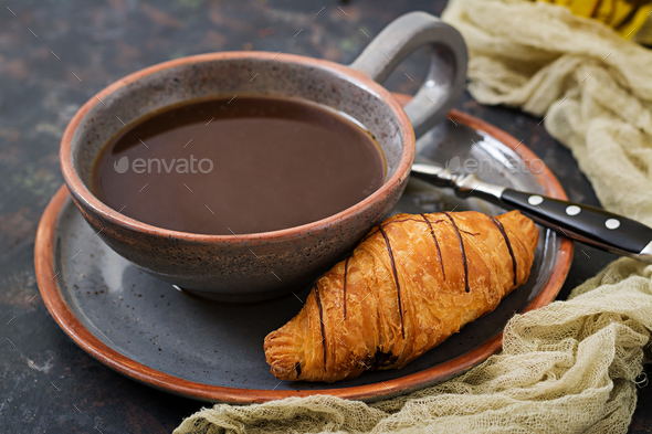 Cup of fragrant coffee and a croissant. Morning breakfast - Stock Photo - Images