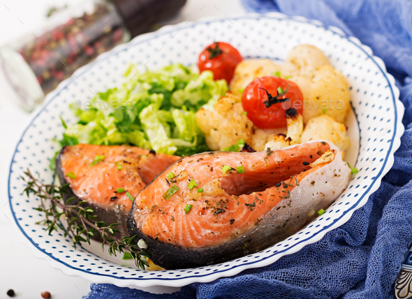Dietary menu. Baked salmon steak with cauliflower, tomatoes and herbs. - Stock Photo - Images